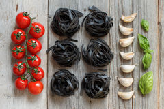 Black Tagliatelle pasta with cherry tomatoes, garlic and basil Stock Photo
