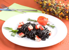 Black tagliatelle pasta with crab cubes. In a plate Royalty Free Stock Photo