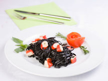 Black tagliatelle pasta with crab cubes. In a plate Stock Photography