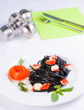 Black tagliatelle pasta with crab cubes. In a plate Royalty Free Stock Photos