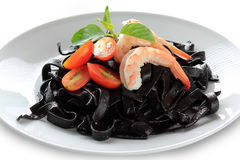 Black tagliatelle with tomato. Black tagliatelle (pasta made with cuttlefish ink) with raw tomato Stock Images