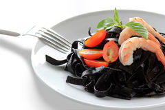 Black tagliatelle with tomato. Black tagliatelle (pasta made with cuttlefish ink) with raw tomato Stock Image