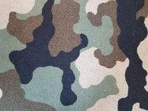 Black, tan, and green camouflage carpet Stock Photos