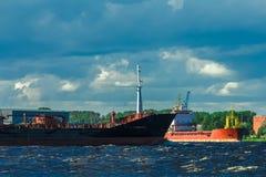 Black tanker ship. Black cargo tanker ship moving past the cargo port Royalty Free Stock Images