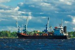 Black tanker ship. Black cargo tanker ship moving past the cargo port Stock Image
