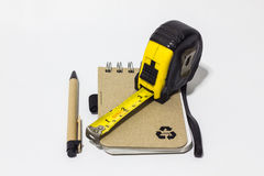 Black tape measure accessories, notebook, pen on background whit. Black tape measure accessories, notebook, pen Royalty Free Stock Photo