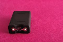 A black taser. Against a pink background royalty free stock image