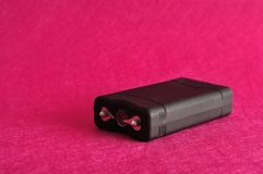 A black taser. Against a pink background royalty free stock photography