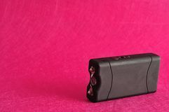 A black taser. Isolated against a pink background stock photos