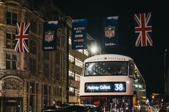 Black taxi and bus on Regent Street decorated with NFL flags, London, UK. London, UK - December 17, 2018: Black taxi and bus on Regent Street, London, in the stock photo