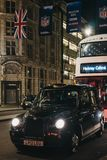 Black taxi and bus on Regent Street, London, under NFL flags, in the evening. London, UK - December 17, 2018: Black taxi and bus on Regent Street, London, in the stock images