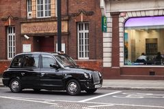 Black taxi cab by The London Taxi Company. London, United Kingdom - October 31, 2017: Black taxi cab by The London Taxi Company is on the street royalty free stock photo