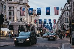 Black taxi and cars on Regent Street, London. The street is decorated with NFL flags to celebrate the event and four NFL games played in capital in 2017 royalty free stock photography