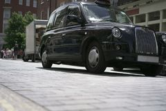Black taxi on London street. Black taxi car stands at street in London stock image