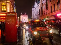 Black taxi at night in Piaccadilly Circus. UNITED KINGDOM, LONDON - APRIL 3, 2015: London black taxi and iconic red phone booth at night in Piaccadilly Circus stock images