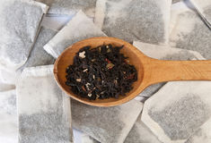 Black tea. Wooden spoon with black tea on a background of tea bags Stock Photos