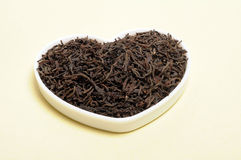 Black tea. Leaf on heart shaped cup royalty free stock images