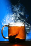 Black tea. A cup with tea stands on a dark blue background. steam rises from a cup royalty free stock photos
