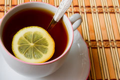 Black tea. Cup of black tea with lemon - close-up royalty free stock image