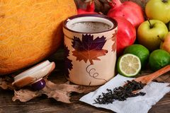 Black tea and autumn colorful fruits Stock Images