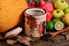 Black tea and autumn colorful fruits Stock Image