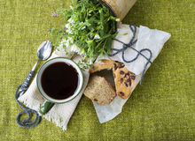 Black tea on a background of green textiles, a bouquet of flowers. Stock Photography
