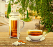 Black tea bags with cup and french press on background Royalty Free Stock Photos