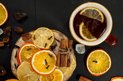 Black tea in a brown earthenware mug with slices of fruit Royalty Free Stock Photo