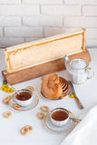 Black tea with buns and honey in honeycomb, whate background Royalty Free Stock Photo