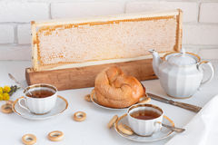Black tea with buns and honey in honeycomb, whate background Royalty Free Stock Image