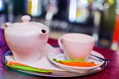 Black tea in a ceramic teapot on a tray with a cup.  Royalty Free Stock Photography