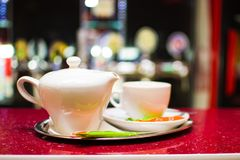 Black tea in a ceramic teapot on a tray with a cup.  Royalty Free Stock Photo