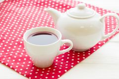 Black tea ceremony - a cup of tea, teapot, flowers on a red with white dots background. Top view, closeup royalty free stock photography