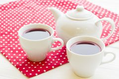Black tea ceremony - a cup of tea, teapot, flowers on a red with white dots background. Top view, closeup stock photography