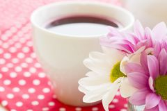 Black tea ceremony - a cup of tea, teapot, flowers on a red with white dots background. Top view, closeup stock image