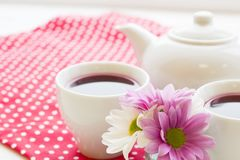 Black tea ceremony - a cup of tea, teapot, flowers on a red with white dots background. Top view, closeup royalty free stock photo