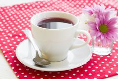 Black tea ceremony - a cup of tea, teapot, flowers on a red with white dots background. Top view, closeup royalty free stock image