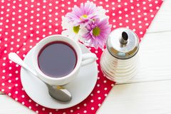 Black tea ceremony - a cup of tea, teapot, flowers on a red with white dots background. Top view, closeup stock photo
