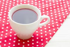 Black tea ceremony - a cup of tea, teapot, flowers on a red with white dots background. Top view, closeup royalty free stock images