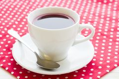 Black tea ceremony - a cup of tea, teapot, flowers on a red with white dots background. Top view, closeup stock images