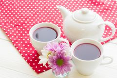 Black tea ceremony - a cup of tea, teapot, flowers on a red with white dots background. Top view, closeup royalty free stock photos