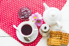 Black tea ceremony - a cup of tea, teapot, sugar, cakes, flowers on a red with white dots background. Top view, closeup royalty free stock photography