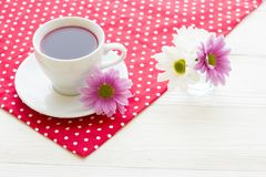 Black tea ceremony - a cup of tea, teapot, sugar, cakes, flowers on a red with white dots background. Top view, closeup stock photography
