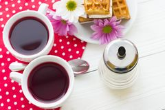 Black tea ceremony - a cup of tea, teapot, sugar, cakes, flowers on a red with white dots background. Top view, closeup royalty free stock photo