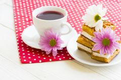 Black tea ceremony - a cup of tea, teapot, sugar, cakes, flowers on a red with white dots background. Top view, closeup stock photo