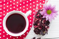 Black tea ceremony - a cup of tea, teapot, sugar, cakes, flowers on a red with white dots background. Top view, closeup stock image