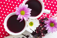 Black tea ceremony - a cup of tea, teapot, sugar, cakes, flowers on a red with white dots background. Top view, closeup royalty free stock photos