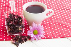 Black tea ceremony - a cup of tea, teapot, sugar, cakes, flowers on a red with white dots background royalty free stock image