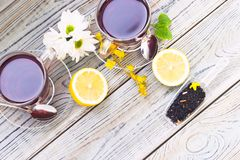 Black tea ceremony - glass full of tea, glass pot, sugar, yellow lemon, flower, tea leaves, spices on a wooden boards background stock photography