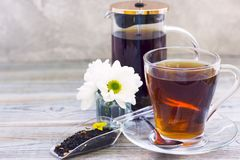 Black tea ceremony - glass full of tea, glass pot, sugar, yellow lemon, flower, tea leaves, spices on a wooden boards background stock photo